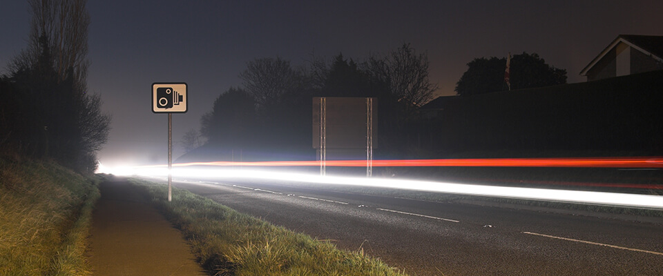 Long exposure speeding car lights with speed camera sign