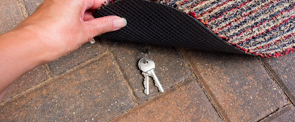 Woman putting house keys under dootmat
